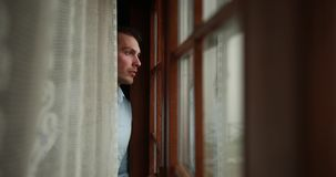 Loneliness in the mountains. Handsome young man opens a curtain and looks sad at the landscape outside.  stock video
