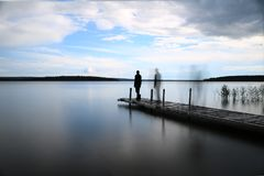 Loneliness. Multiple exposure of a silhouetted man walking on a pier at the lake Royalty Free Stock Photo