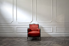 Loneliness. Red armchair in a big white room Royalty Free Stock Images