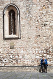 Loneliness retired elderly man reading newspaper. Ancient wall and window Royalty Free Stock Photo