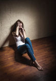 Loneliness. Sad woman sitting alone in a empty room Stock Photos