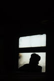 Loneliness. The silhouette of a lone men in the window of a train Stock Photos