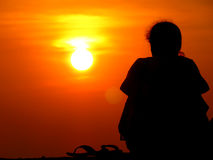 Loneliness. A silhouette of lonely woman sitting alone watching the sunset Stock Photography