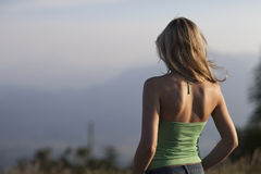 Loneliness. Solitary young woman with long blond hair standing with her back to the camera looking out over a misty mountain view deep in contemplation in a stock photos