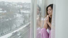Loneliness solitude relaxing leisure girl window. Loneliness solitude. relaxing leisure. young beautiful teen girl sitting on the windowsill and looking out of stock video footage