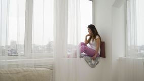 Loneliness solitude relaxing leisure girl window. Loneliness solitude. relaxing leisure. young beautiful teen girl sitting on the windowsill and looking out of Royalty Free Stock Photo