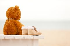 Loneliness teddy bear and baby's bootees stay on a sunbed. On the ocean beach. Concept about childhood, loneliness and expectancy Royalty Free Stock Image