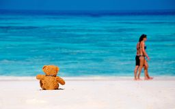 Loneliness Teddy Bear sitting on the beach. Teddy Bear sitting on the beach with blue sea and sky background. Concept about loneliness and expectancy Stock Image
