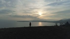 One hike man walking on the hill to lake at sunset. Loneliness trip concept: climbing at spring time. Back view: one guy going on the hilly field to waterfront stock footage