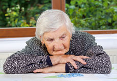 Loneliness. Unhappy elderly woman sitting at the table Royalty Free Stock Images