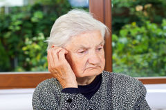 Loneliness. Unhappy elderly woman sitting at the table Royalty Free Stock Photography
