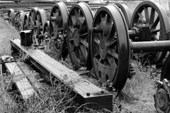 Railway axles. In a warehouse of old locomotives, this strange composition of lonely axles bring us back to the beginning of the industrial age now past Stock Photo