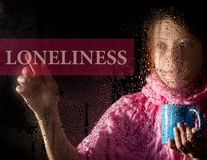 Loneliness written on virtual screen. young woman melancholy and sad at the window in the rain, she holding a cup of hot Stock Photos