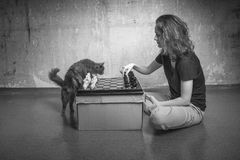 Loneliness - is when you're playing chess with cat. Young girl playing chess with a cat in an old empty room royalty free stock images
