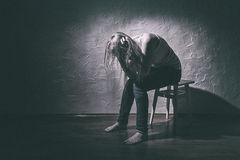 Loneliness. Young sad woman sitting alone in a chair in an empty room Royalty Free Stock Image