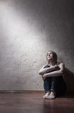 Loneliness. Young sad woman sitting alone on the floor in an empty room Stock Images