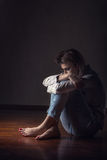 Loneliness. Young sad woman sitting alone on the floor in an empty room Stock Image