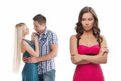 Loneliness. Young sad women standing with her arms crossed while another women and men hugging Royalty Free Stock Image