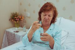 Lonelly senior woman drinking medecine. royalty free stock photography