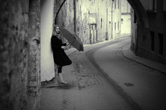 Lonelly woman with umbrella in a street, retro Royalty Free Stock Photography