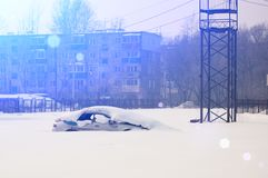 Lonely abandoned snow-covered car in parking lot on winter sunny day.  stock photos