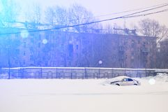 Lonely abandoned snow-covered car in parking lot on winter sunny day.  royalty free stock image