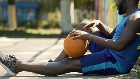 Lonely Afro-American basketball player sitting on ground with ball, sadness. Stock photo stock photography