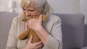 Lonely aged mother embracing teddy bear, remembering busy children, memories. Stock footage stock footage