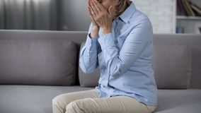 Lonely aging lady on sofa covering face, overwhelming problems, bad news stock photography