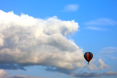 Lonely air baloon flying in front of white puffy clouds against Royalty Free Stock Photo
