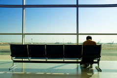 Lonely airport passenger. A lonely and jetlagged passenger sitting and resting in a seats row in front of a sunny window facing the tarmac and airplanes on an Stock Images