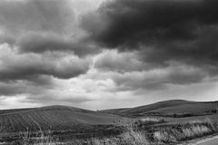 Lonely Art Nature Hills under cloudy sky. Stormy weather black and white image Stock Photos