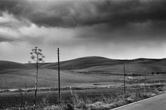 Lonely Art Nature Hills under cloudy sky. Stormy weather black and white image Stock Images