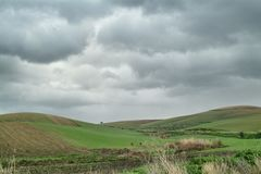 Lonely Art Nature Hills under cloudy sky. Stormy weather color image Royalty Free Stock Image