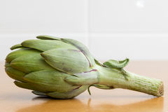 Lonely artichoke on wooden table Royalty Free Stock Photography