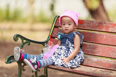 Lonely Asian baby girl sitting with beverage Stock Images