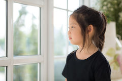 Lonely Asian Child Looking Out Window. Expressing her emotion Royalty Free Stock Images