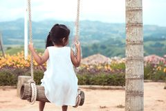 Lonely asian little child girl sitting on wooden swings. And looking at nature view in playground Stock Photos