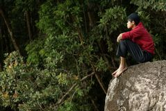 Lonely asian man sitting on rock Royalty Free Stock Image