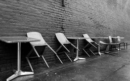 Lonely Avenue. Rainy morning lonely chairs outside coffee shop Stock Photos