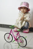 A lonely baby. With a little bicycle Royalty Free Stock Photos