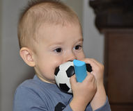 Lonely baby with a ball. Portrait of a baby with a toy in his mouth Stock Photography