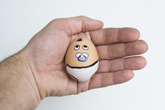 Lonely baby egg face in man hand Royalty Free Stock Photos