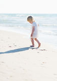 Lonely baby playing on sea shore Stock Images
