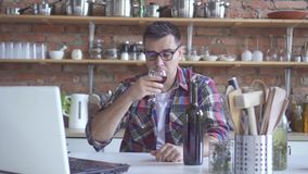 Lonely bachelor man in the kitchen drinking wine and looking at a white laptop stock footage