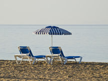 Lonely Beach. Inviting image of a lonely beach, with two sun beds and a umbrella Royalty Free Stock Photography