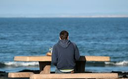 Lonely Beach. A man sits alone on a bench at the beach Stock Photo