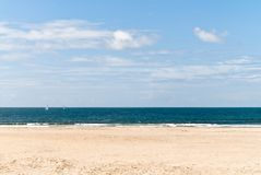 Lonely beach. And the sail on the horison in Portugal Royalty Free Stock Image