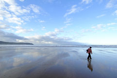 Lonely on Beach. Girl strolling along a deserted Woolacombe Beach in winter Stock Photos