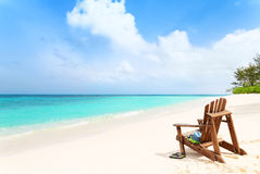 Lonely beach chair with hat and slippers at tropical beach, summ Stock Images